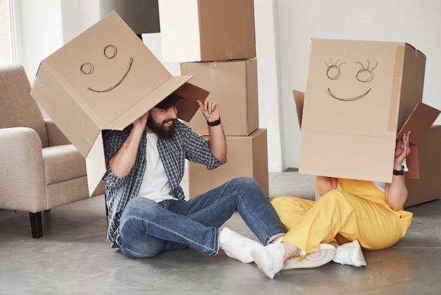 Jugando con cajas. pareja feliz juntos en su nueva casa. concepción de mudanza