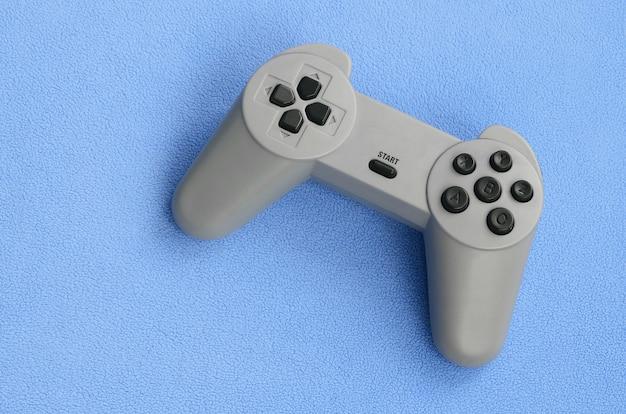 Jugando concepto de juegos. el joystick de una sola almohadilla se encuentra en la manta de un tejido azul velludo peludo