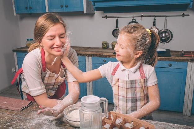 Jugando con harina. cocinar pasteles caseros. feliz familia amorosa están preparando panadería juntos. madre e hija hija están cocinando galletas y divirtiéndose en la cocina