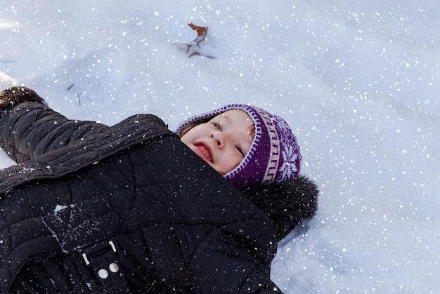 Jugando en la nieve niño pequeño en una clara nieve blanca