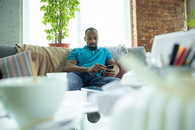 Jugando en el teléfono inteligente, navegando en línea. hombre afroamericano que se queda en casa durante la cuarentena debido a la propagación del coronavirus, covid-19. tratando de divertirme. concepto de salud y medicina.