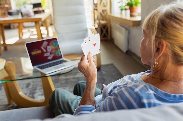 Jugar al póquer casino online senior mujer estudiando en casa obteniendo cursos online