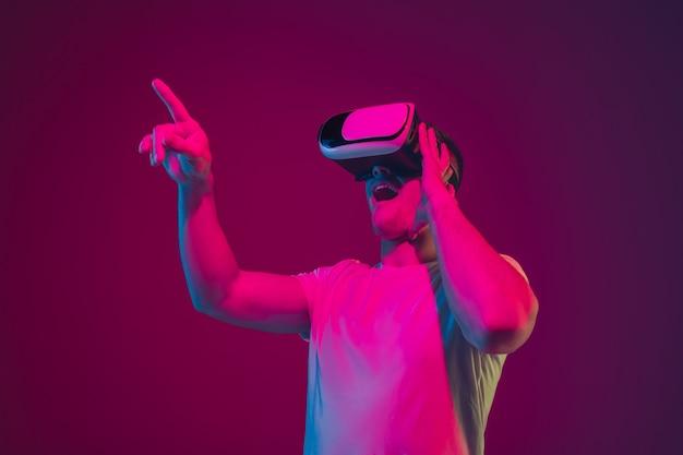 Jugar con realidad virtual, disparar, conducir. retrato de hombre caucásico aislado en la pared del estudio de color rosa-violeta.