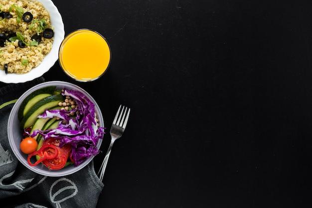 Jugo; budín de chía y ensalada de verduras frescas sobre fondo negro