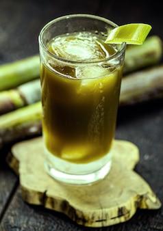 Jugo de caña de azúcar, jugo verde dulce, rico en acarosi, sobre mesa de madera rústica