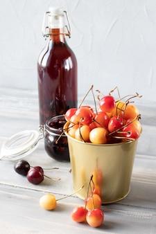 Jugo casero y mermelada de cerezas, bayas en un cubo pequeño
