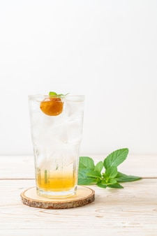 Jugo de ciruela helado con soda y menta en la mesa de madera - bebida refrescante