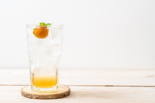 Jugo de ciruela helado con soda y menta en mesa de madera. bebida refrescante
