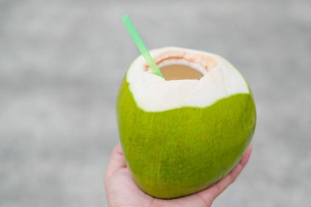 Jugo de coco aromático fresco, fruta de coco en la mano con desenfoque de fondo.