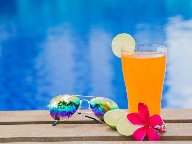 Jugo de naranja con gafas de sol en el lado de la piscina. vacaciones, concepto de verano