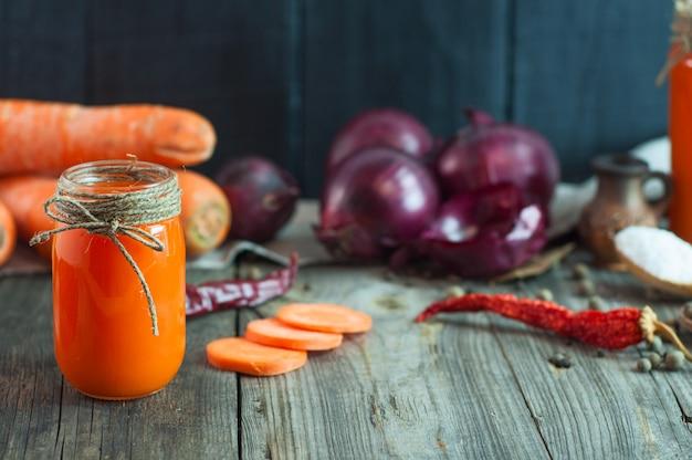 Jugo fresco de zanahoria en un recipiente de vidrio entre las verduras