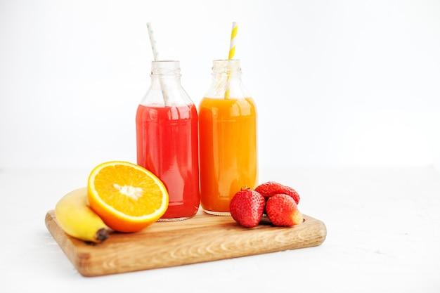 Jugo de frutas en botellas. plátano, naranja. verano y fiesta.