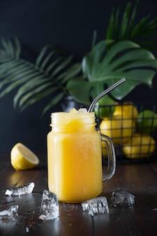 Jugo de frutas frescas de verano con limón sobre fondo tropical oscuro. de cerca.