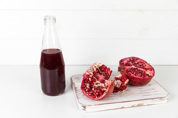 Jugo de granada fresca en botella en la mesa