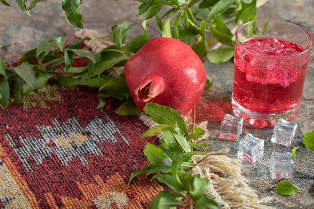 Jugo helado y granada con hojas y alfombra sobre superficie de piedra