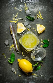 Jugo de limón en el frasco con la ralladura, las hojas y el hielo alrededor. sobre la mesa de piedra. vista superior