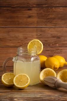 Jugo de limón en el recipiente de vidrio con frutas sobre la mesa de madera