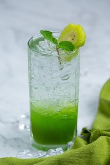 Jugo de manzana fresco en un vaso con manzanas verdes.