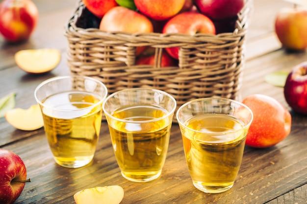 Jugo de manzanas en vaso con manzana en la cesta