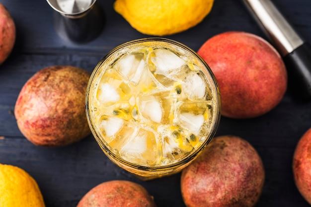 Jugo de maracuyá fresco y saludable con maracuyá y limón en el fondo.