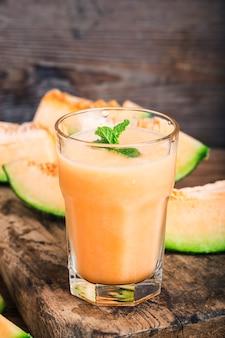 El jugo de melón con menta en un frasco de vidrio sobre la mesa. hami melon