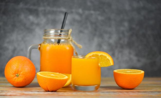 Jugo de naranja en el frasco de vidrio y rodaja de naranja fresca en mesa de madera