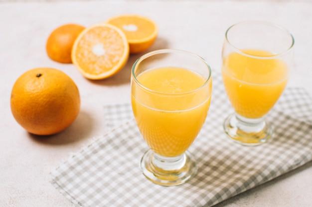 Jugo de naranja fresco de alto ángulo en vaso