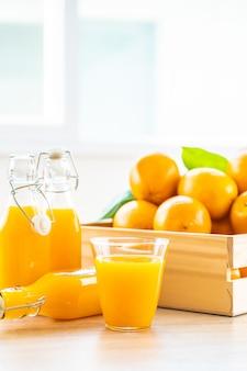 Jugo de naranja fresco para beber en botella de vidrio