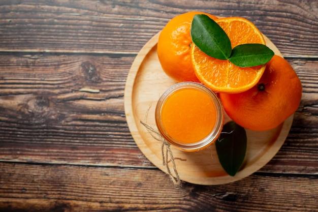 Jugo de naranja fresco en el vaso sobre fondo de madera oscura.