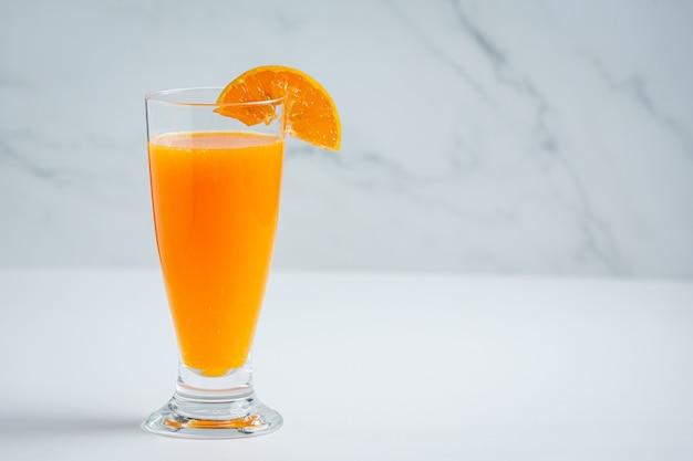 Jugo de naranja fresco en el vaso sobre fondo de mármol