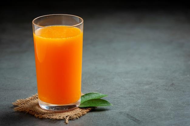 Jugo de naranja fresco en el vaso sobre fondo oscuro