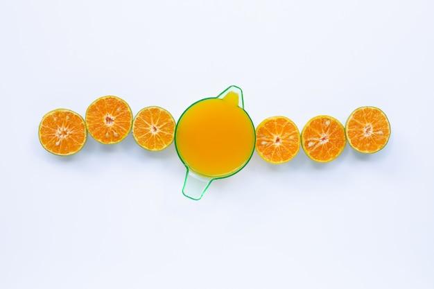 Jugo de naranja con naranjas de medio corte en blanco
