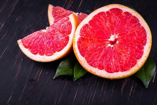 Jugo de naranja y pomelo sobre un fondo negro de madera