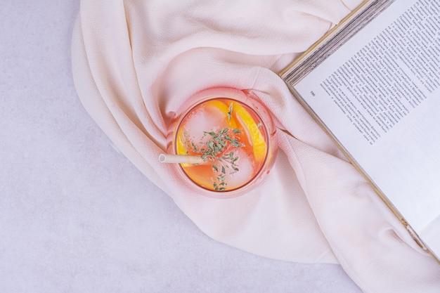 Jugo de naranja con rodajas de frutas y especias en mesa blanca.