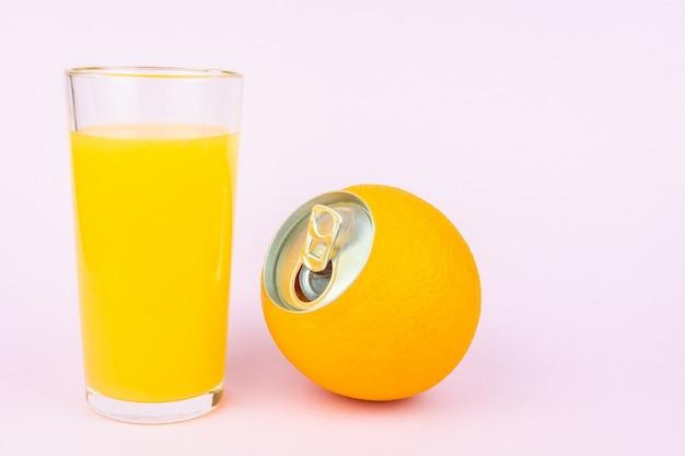 Jugo de naranja sobre fondo rosa