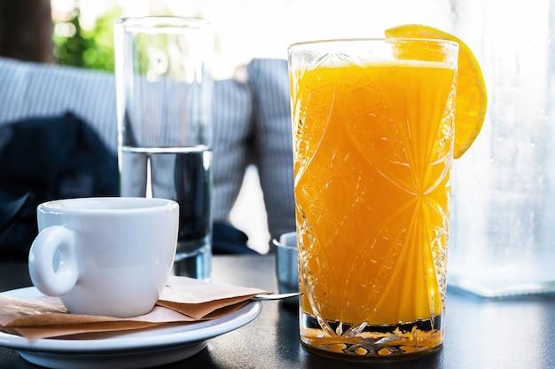 Jugo de naranja y una taza de café en un restaurante.