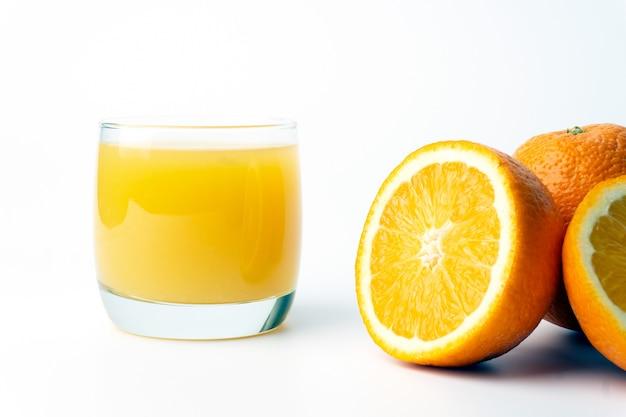 Jugo de naranja en una taza de vidrio transparente con naranjas frescas.