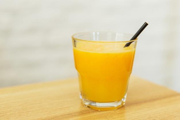 Jugo de naranja en un vaso en la mesa de madera en un restaurante