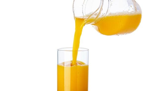 Jugo de naranja vertido de la jarra en vidrio sobre superficie blanca