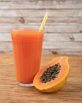 Jugo de papaya en un vaso con frutas sobre mesa de madera.