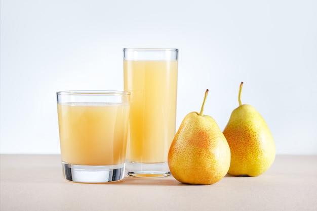 Jugo de pera con frutas frescas en la mesa de la cocina. bebida saludable.