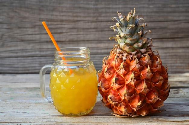 Jugo de piña recién exprimido en una taza de vidrio con pajita y fruta madura de ananas en la mesa de madera vieja. concepto de comida sana, dieta o comida vegana.