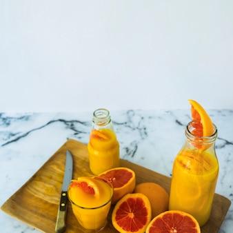 Jugo de pomelo casero en vidrio y botellas en una tabla de cortar con un cuchillo afilado
