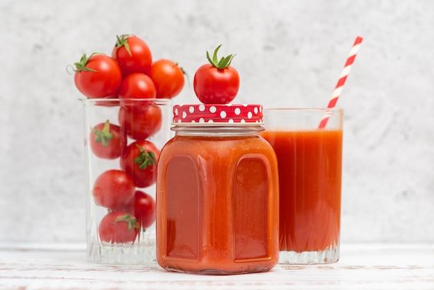 Jugo de tomate fresco en vasos y tomates cherry a la luz.
