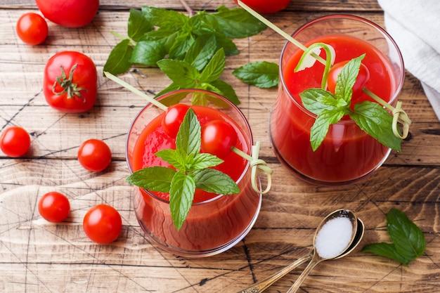 Jugo de tomate con menta en vidrio y tomates frescos en una mesa de madera. concepto de comida orgánica saludable.