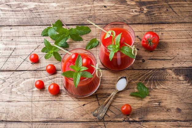Jugo de tomate con menta en vidrio y tomates frescos en una mesa de madera