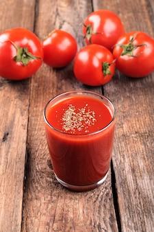 Jugo de tomate con tomates rojos frescos en una mesa de madera.