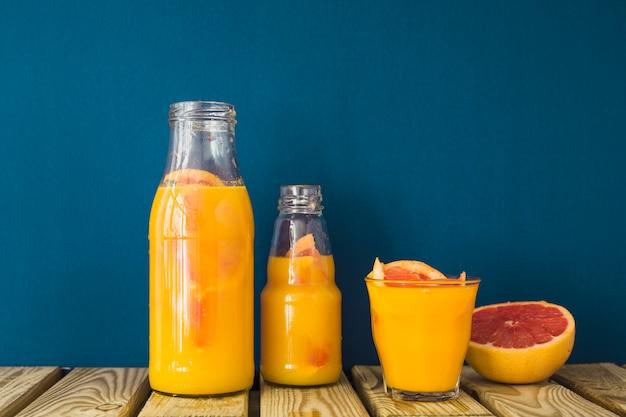 Jugo de toronja en botella y vaso en mesa de madera con fondo azul
