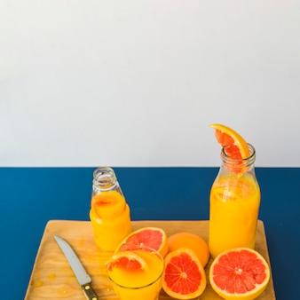Jugo de toronja en botella y vaso en la tabla de cortar contra el fondo azul