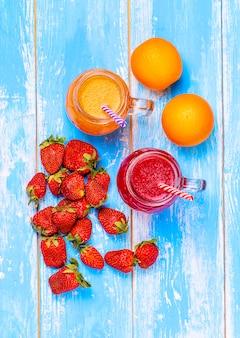 El jugo de toronja y naranja, fresas y naranja sobre una mesa azul